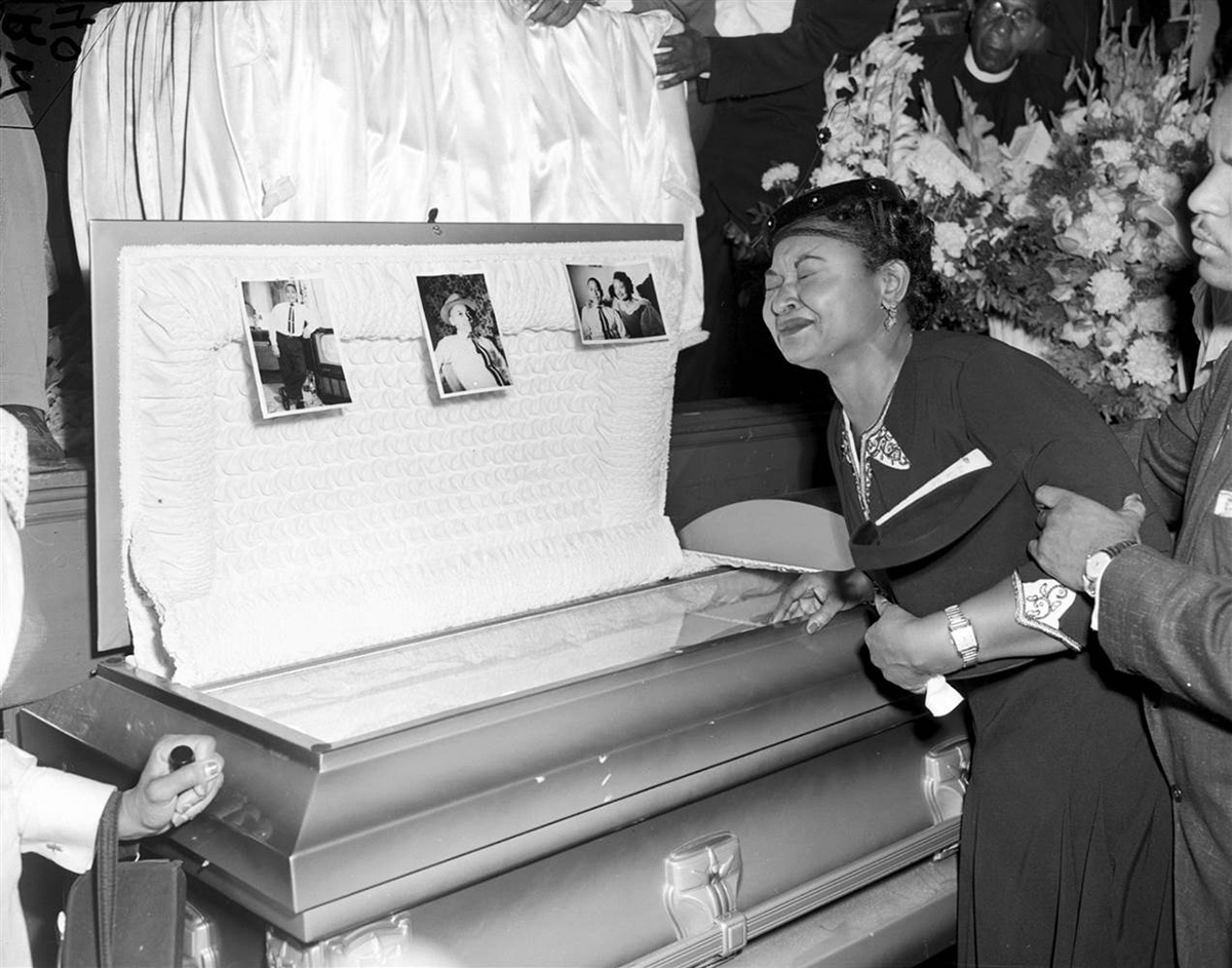Mamie Bradly leaning on her son's casket which is currently on exhibit at the National Museum of African American History